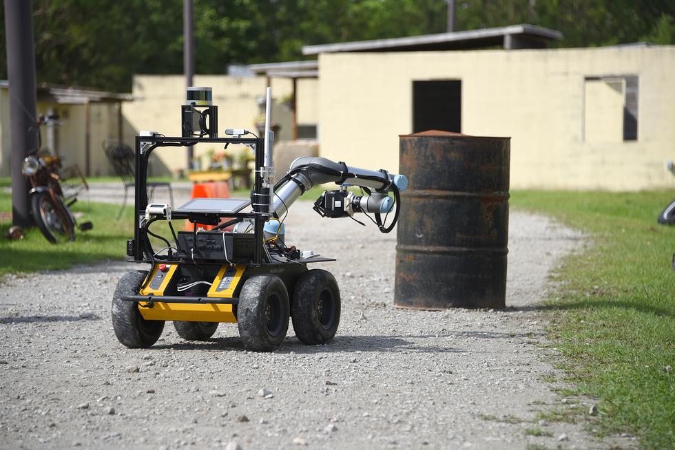 A robot moving towards a metal drum.